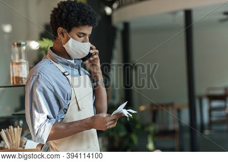 Worried New Business Owner Calculating Finances. Young African American Male In Apron And Protective