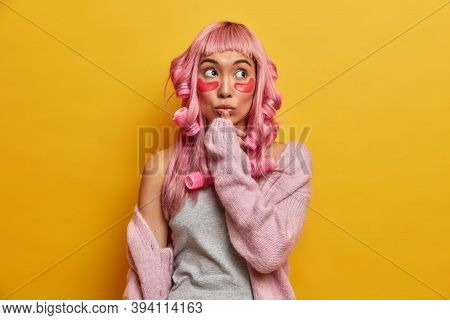 Thoughtful Asian Woman With Pink Hair, Prepares For Special Occasion, Applies Collagen Pads And Hair
