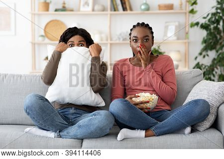 Frightened Black Girlfriends Watching Horror Together At Home, Eating Popcorn. Scared African Americ