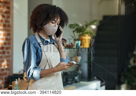 Concentrated African American Administrative Manager Of Cafe In Protective Mask Make Revisions After