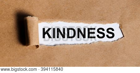 Kindness. Text On White Paper On Torn Paper