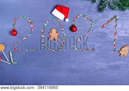 New Year Background With 2021 Made With Sugar Sprinkle. Gingerbread Cookies, Santa Hat, Bauble And L