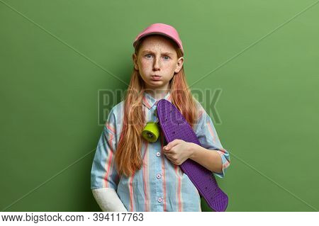 Sullen Displeased Preteen Girl Skateboarder Poses With Skateboard, Has Bad Mood After Breaking Arm D