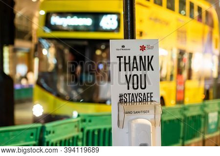 London - November 3, 2020: Hand Sanitiser Station With Out Of Focus London Double Decker Bus In The