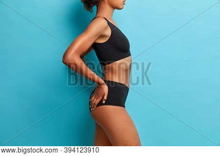 Sexual Slim Woman Stands In Profile Wears Black Sport Clothes Poses Against Blue Background. Attract