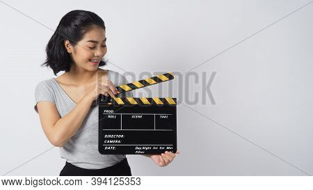 Girl Or Woman Wearing Braces And Contact Lenses. Her Hand's Holding Black Clapper Board Or Movie Sla