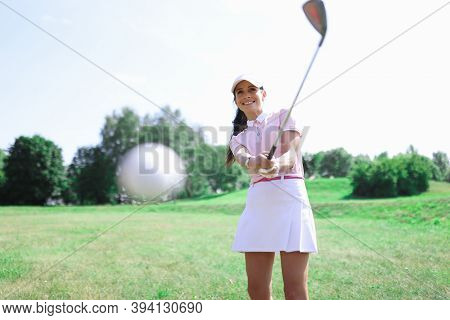 Woman Golfer Makes A Hit With A Club On Ball. Golf Game And Everyday Hobby Concept