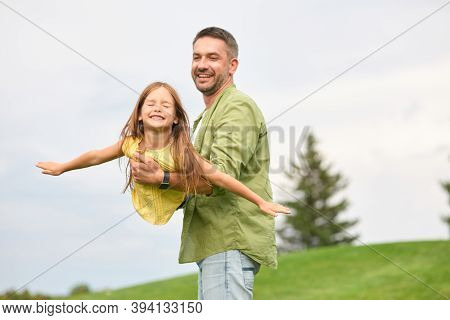 Happy Father Holding His Little Daughter, Having Fun Together. Joyful Girl Playing With Her Daddy In