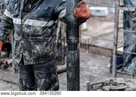 Work Driller In Red Uniform, In Helmet And Goggles. He Uses A Hydraulic Wrench To Screw Drill Pipes