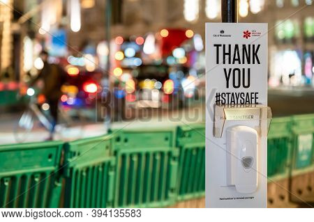 London - November 3, 2020: Hand Sanitiser Station With Out Of Focus Traffic Headlights In The Backgr