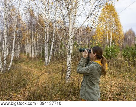 Young Woman Birdwatcher With Binoculars In The Autumn Forest. Birdwatching, Zoology, Ecology. Resear