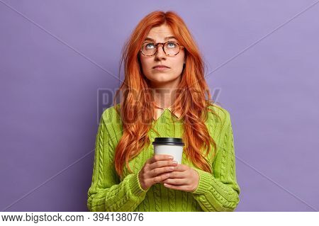 Serious Pretty Redhead Woman Focused Above On Ceiling Drinks Take Away Coffee And Wears Green Sweate