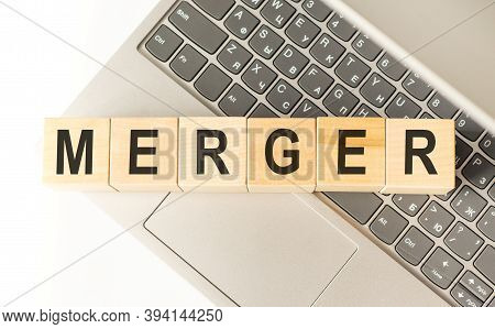 Word Merger. Wooden Cubes With Letters Isolated On A Laptop Keyboard. Business Concept Image.