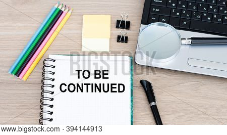 Text To Be Continued On An Open Notebook On An Office Table, Next To A Laptop, A Pen, A Magnifying G