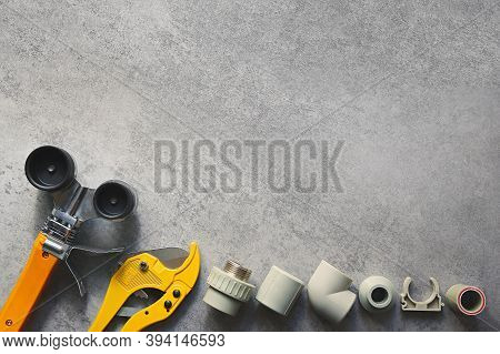 Plumbing Tools On Gray Background With Copy Space. Soldering Iron Scissors And Fittings Pp And Pvc.