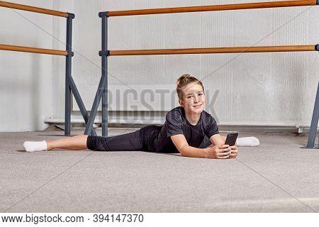 A Man Is Lying On The Floor, Legs Apart. Flexibility And Endurance Training.