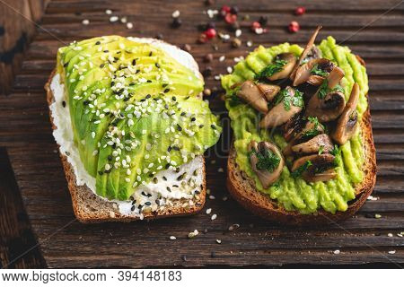 Two Toasts With Avocado, Cream Cheese And Mushrooms Garnished With Sesame Seeds. Top View. Healthy A