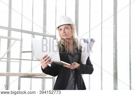 Woman Architect Or Construction Engineer With Computer Laptop Wear Helmet And Holds Blueprint Inside
