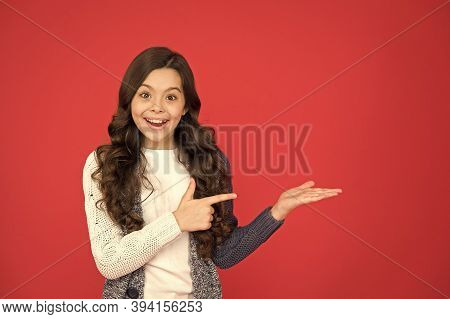 Your Advertisement Or Promotional Text. Happy Kid Pointing At Red Background. Advertising For Produc