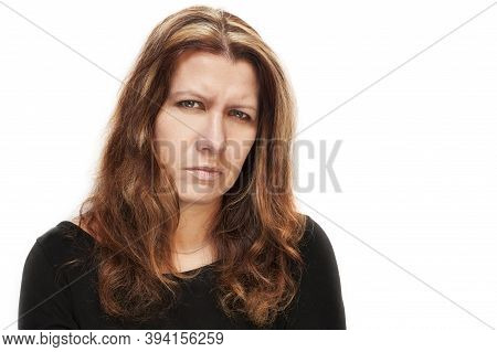 Portrait Of A Sad, Angry Woman On A White Background. She Is Dressed In A Black Shirt. Isolated