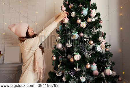 Happy Young Woman Decorates The Christmas Tree Hang The Ball On The Tree. Christmas Decoration, Toys