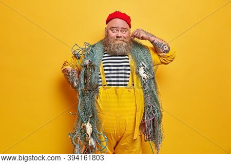 Photo Of Bearded Sailor Man Curls Mustache And Poses Indoor With Fishing Gears Poses Against Yellow