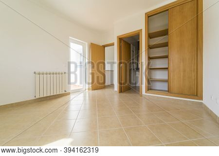 Empty room with dark wooden floating laminate flooring and wardrobe. House interior, wide bedroom space. Newly recently painted new apartment or house. Wood floor. Real state and property management
