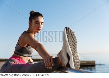Close-up Of Attractive Sportswoman Holding Leg On Handrope, Stretching On The Seaside Promenade. Fem