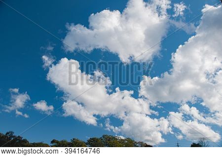 A Beautiful Meteorological Sky Cloudscape Scene, With White  Cumulus Cloud Formation In A Mid Blue S