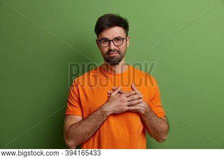 Flattered Pleased Unshaven Guy Presses Hands To Heart, Expresses Heartwarming Feelings And Gratitude