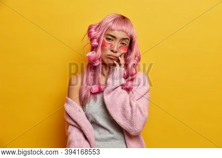 Dejected Upset Woman With Rosy Hair, Tired Of Beauty Procedures, Wears Curlers, Makes Perfect Hairst