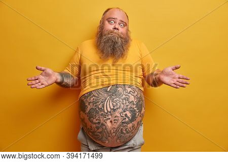 Hesitant Thick Man With Big Tattooed Belly, Shrugs Shoulders And Looks Confused, Faces Dilemma, Make