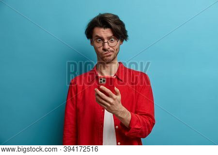 Puzzled Brunet Youngster Concentrated In Smartphone Display, Types Text Message, Connected To Wirele