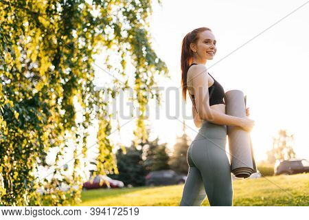 Low-angle Shot Of Young Caucasian Woman Holding Yoga Mat And Smile At City Park, Ready To Practice Y