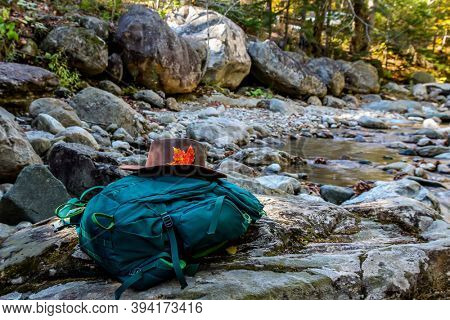 Green backpack with hat in the forest newar river