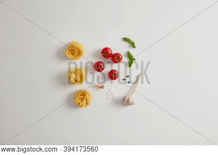 Pasta Ingredients On White Background. Red Cherry Tomatoes, Basil, Garlic, Peppercorns, Uncooked Pas