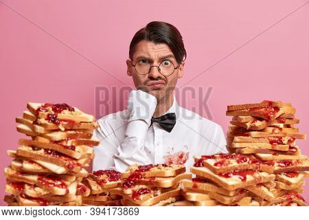 Serious Man Aristocrat Frowns Face, Dressed In Snow White Elegant Clothes, Stands Near Stack Of Deli