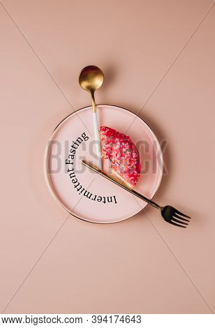 Intermittent Fasting Concept. One-third Donut Symbolizing Eight Hours With Cutlery Like A Clock Hand