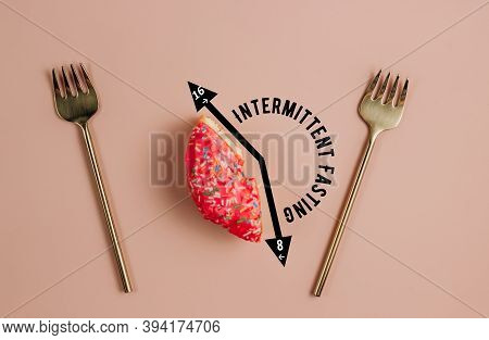 Intermittent Fasting Concept. One-third Donut Symbolizing Eight Hours With Cutlery On Pink Backgroun