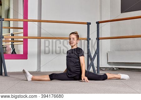 A Guy Very Flexible In The Twine At Ballet School Smiles And Looks At The Camera