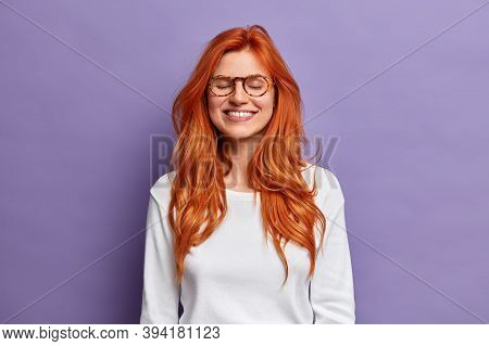 Positive Redhead Woman Expresses Pure Emotions And Happiness, Dressed In Casual White Jumper. Beauti