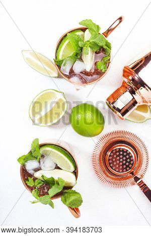 Moscow Mule Cocktail In Copper Mug With Lime, Ginger Beer, Vodka And Mint. White Table, Copy Space