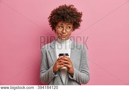 Pensive Dark Skinned Curly Female Entrepreneur Holds Disposable Cup Of Aromatic Coffee And Has Thoug