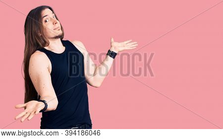 Young adult man with long hair wearing goth style with black clothes clueless and confused expression with arms and hands raised. doubt concept.