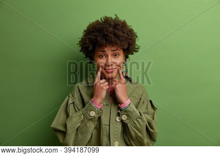 Portrait Of Dark Skinned Woman Touches Fingers Near Corners Of Lips, Pretends Smiling, Has Unhappy E