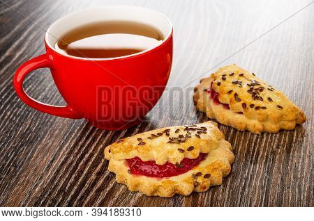 Red Cup With Tea, Shortbread Cookies With Raspberry Jam And Linseeds On Dark Wooden Table
