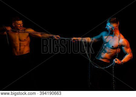 Two Men Broken Chains, Holding Chain. Sexy Torso Of Young Fitness Man With Muscular Strong Abdominal