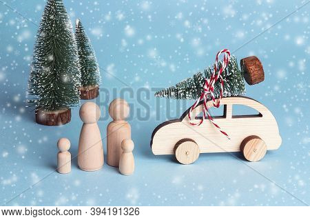 Toy Family And Toy Car With Christmas Tree On The Roof. Wooden Figures Of Father, Mother And Childre