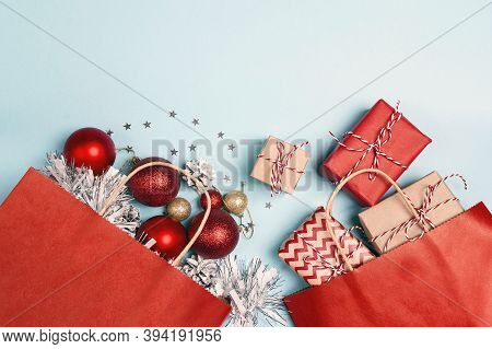 Red Shopping Bags With Christmas Decoration And Gifts  On A Blue Background. Holidays Shopping And D