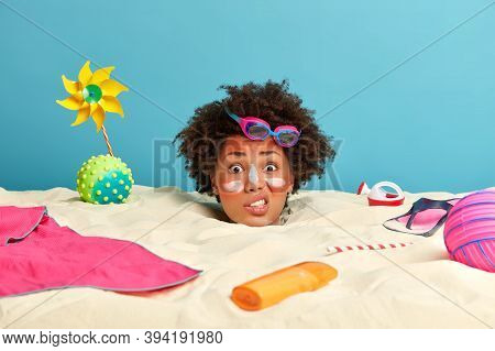Summer Lifestyle And Recreation Concept. Worried Displeased Woman Buried In Sand, Spends Much Time A